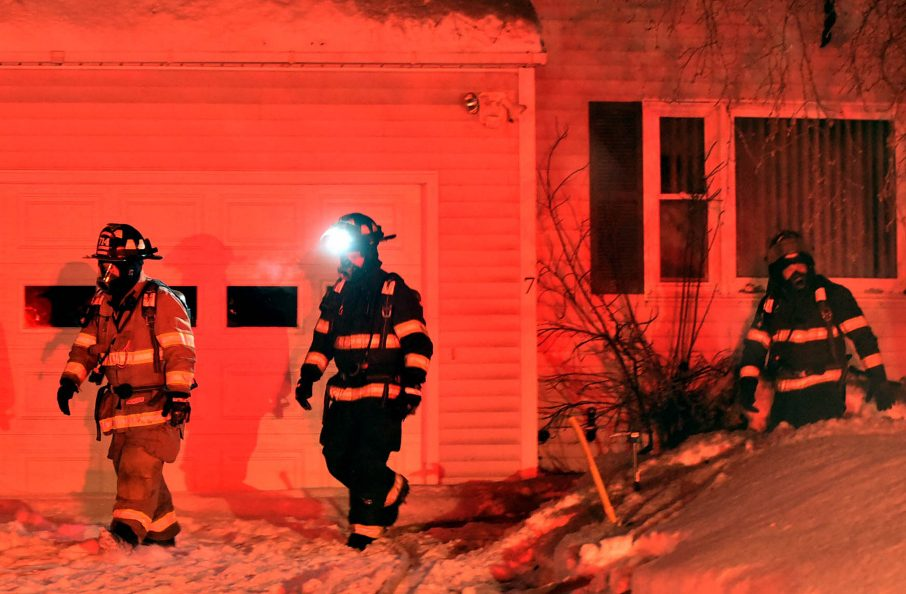 Firefighters look for remnants of a small house fire Saturday evening on John Avenue in Waterville.