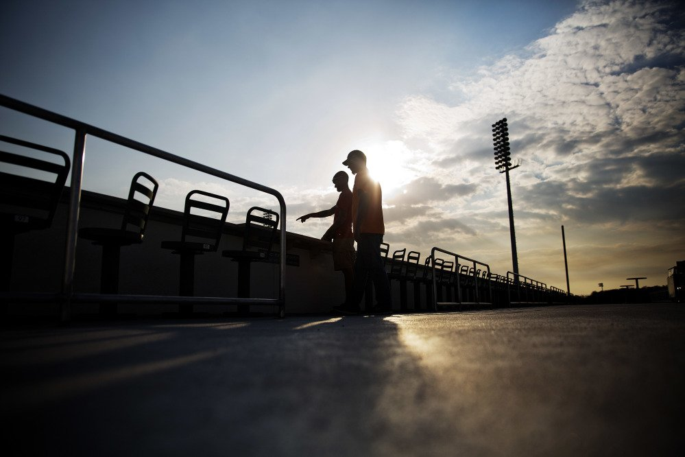 Stadium workers look out over the field at JetBlue Park at Fenway South, the spring training ballpark of the Boston Red Sox, as the sun sets in Fort Myers, Florida on Monday.