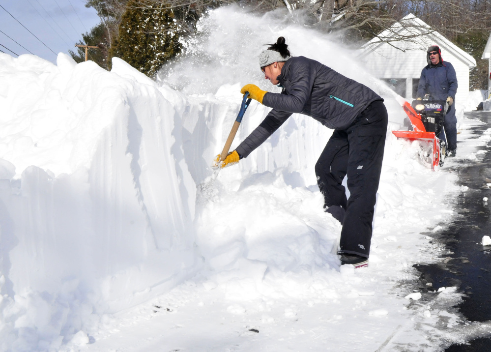 Ashley Conners chops away at a wall of snow as her father, Glenn, uses a snowblower to clear their driveway Tuesday of the 30 inches of snow that fell in Starks.