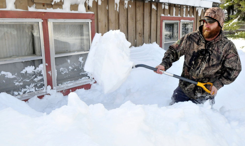 "Ryan Andrews shovels snow that piled up as high as his windows on his home in Starks while clearing snow Tuesday. Andrews said he has cleared snow from around his home and roof for four hours. ""This is an overwhelming amount of snow,"" Andrews said."
