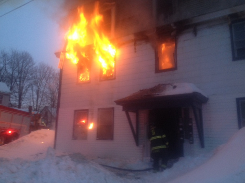 Flames spill out from the windows Tuesday evening of an apartment building at 11 Main St. in Skowhegan.