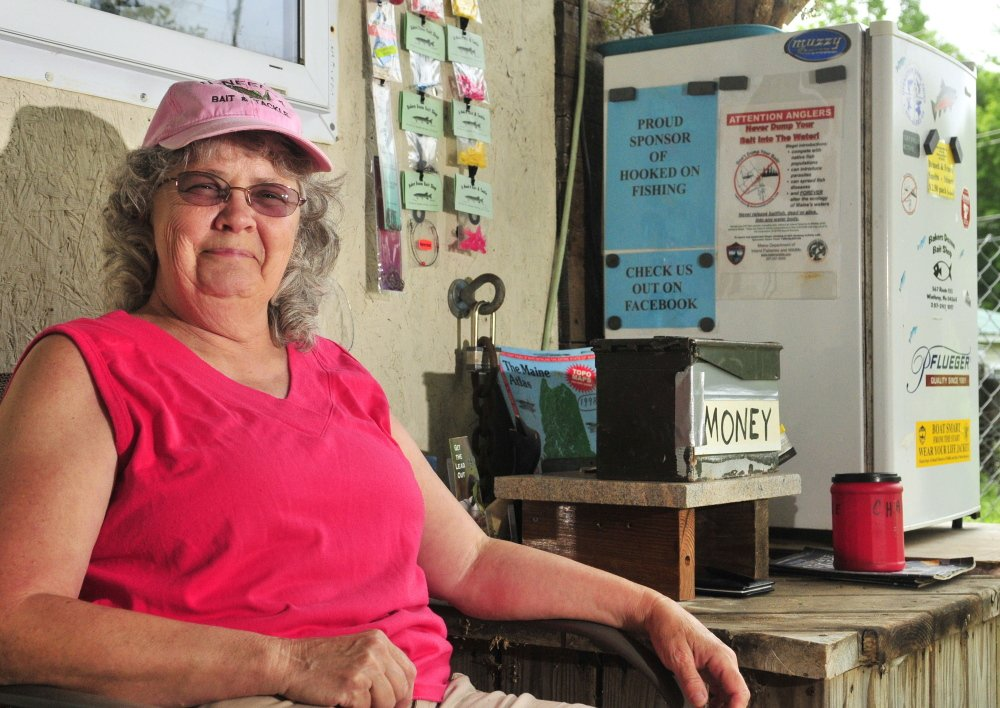 June Bubier sits beside a self-serve refrigerator full of bait in July 2014 on the porch at Bakers Dozen Bait Shop, the store in Winthrop that she owned with her husband David. Bubier was selected Tuesday night to serve on the Winthrop Town Council as a short-term replacement for her husband, who died in January.