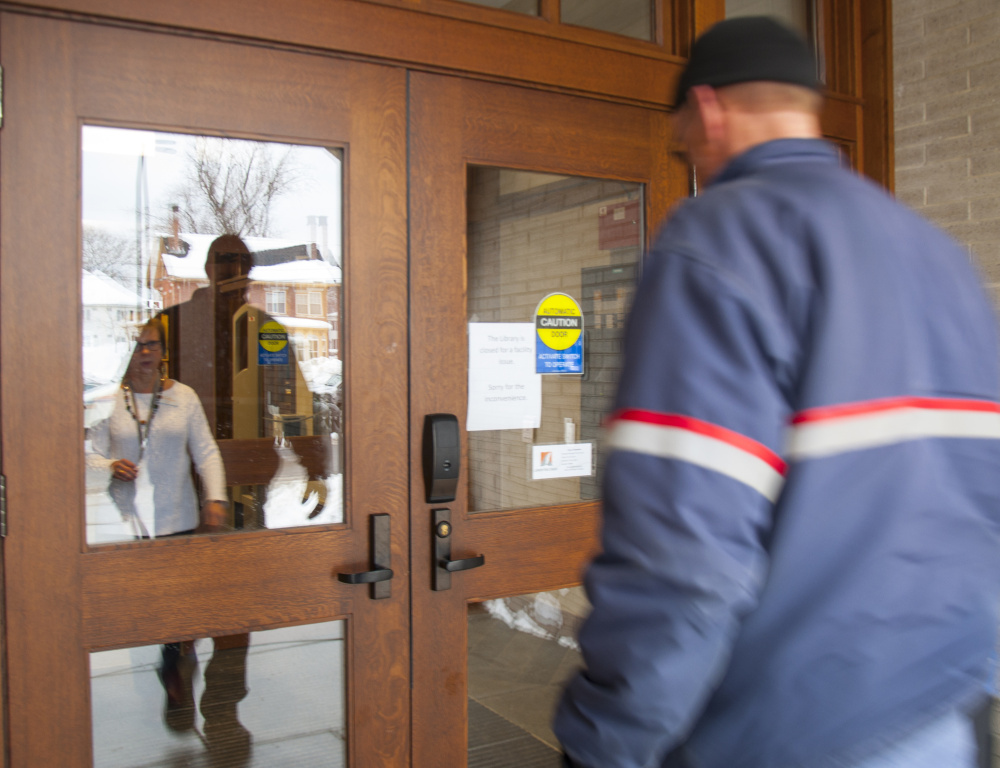 Betsy Pohl, Lithgow Public Library's director, greets the mail carrier Wednesday to let him in while the Augusta library is closed.