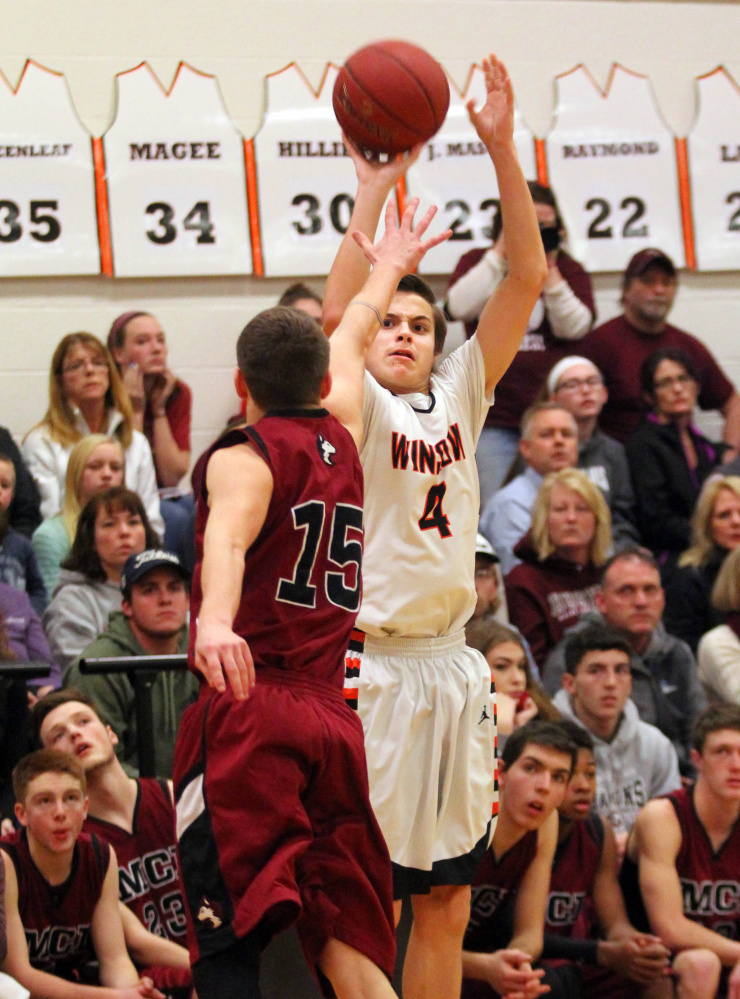 Winslow High School's Spencer Miranda shoots over Maine Central Institute's Josh Buker during the first half of a Class B North prelim game in Winslow on Thursday night.