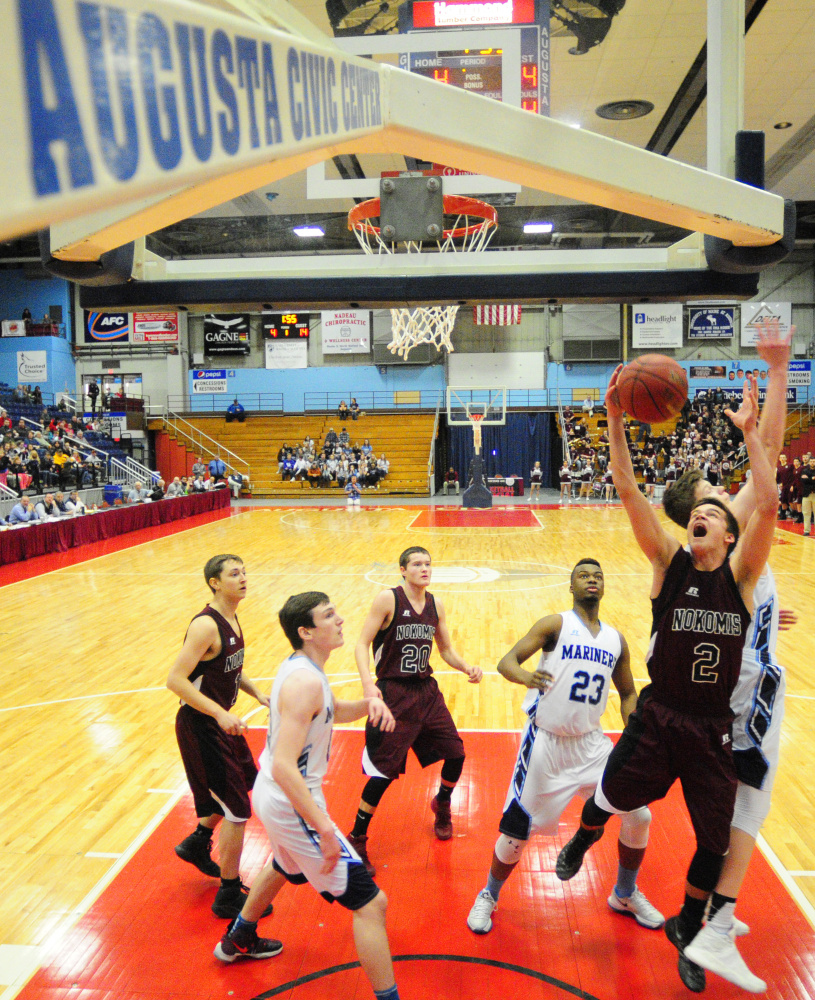 Staff photo by Joe Phelan Nokomis' Joshua Smestad and Oceanside's Cooper Wirkala go for a rebound during a Class A North quarterfinal game Saturday at the Augusta Civic Center.