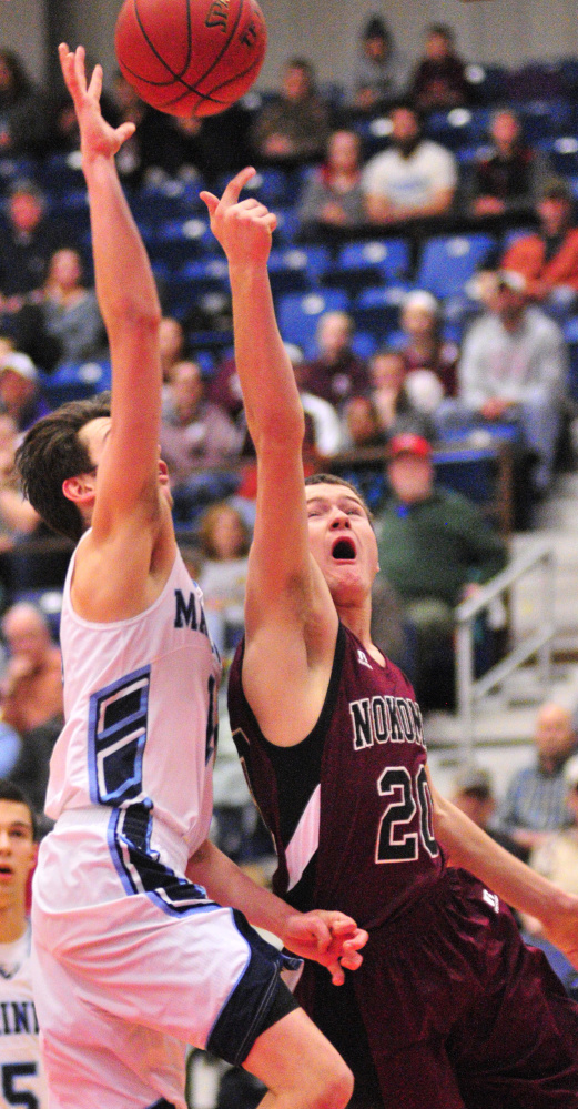 Staff photo by Joe Phelan Oceanside senior guard Sam Atwood, left, tries to block a shot by Nokomis junior guard Zach Hartsgrove during a Class A North quarterfinal game Saturday at the Augusta Civic Center.
