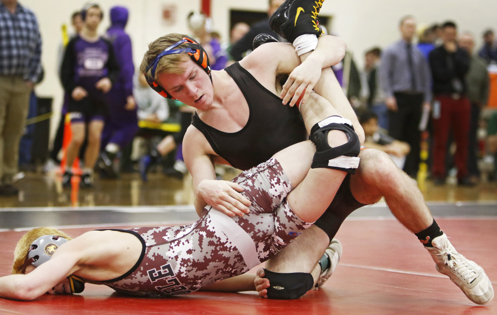Cody Craig of Skowhegan turns Sam Martel of Noble for the pin in the 106-pound weight class finals at the Class A state championships Saturday at Camden Hills Regional High School.