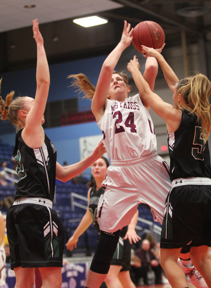 Monmouth Academy's Kaeti Butterfield puts up a shot over Waynflete's Lydia Giguere, left, and Isabel Burdick, right, during the first half a Class C South girls quarterfinal in Augusta on Monday. Monmouth won 45-40.