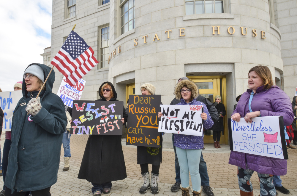 Kathleen Conrad, far left, of North Yarmouth, joins other protesters Monday at the State House in Augusta as part of a rally called Not My President's Day. The event was held to protest immigration restrictions and other policies of the Trump presidency, as well as the president himself.