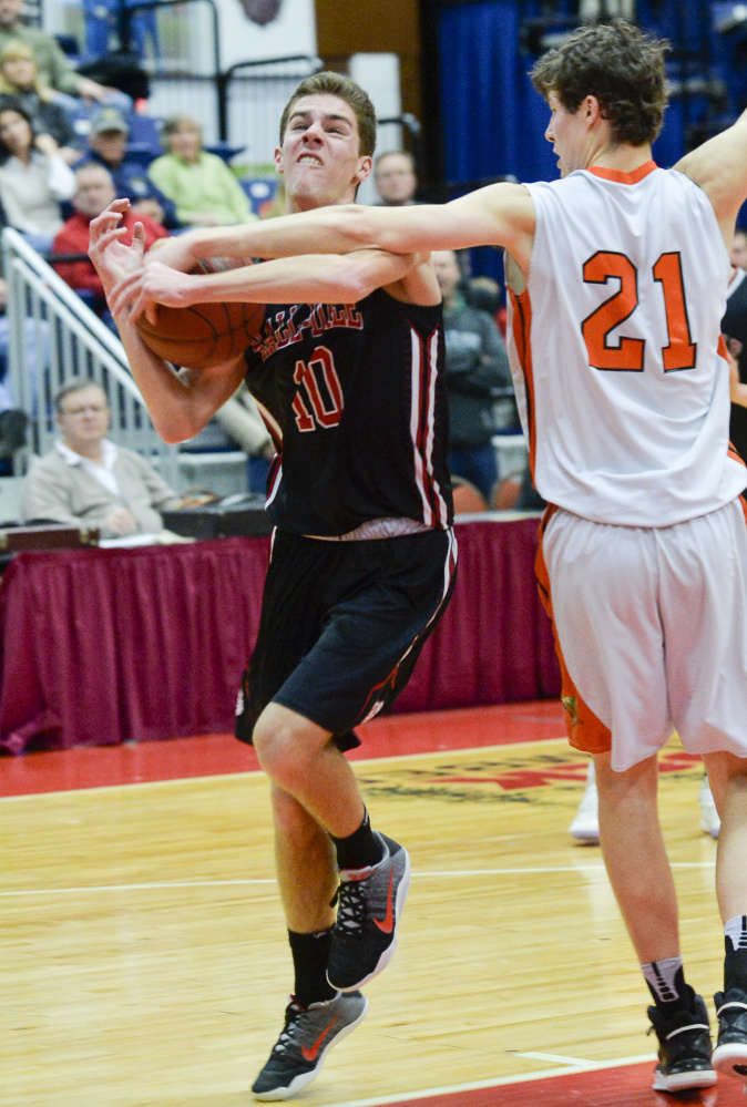 NYA's Jake Malcom (21) gets his hand on the ball as Hall-Dale's Alec Byron goes up for a shot during the first quarter of a Class C South quarterfinal game Monday at the Augusta Civic Center. The shot went wild, but the Bulldogs ended the quarter with a lead.