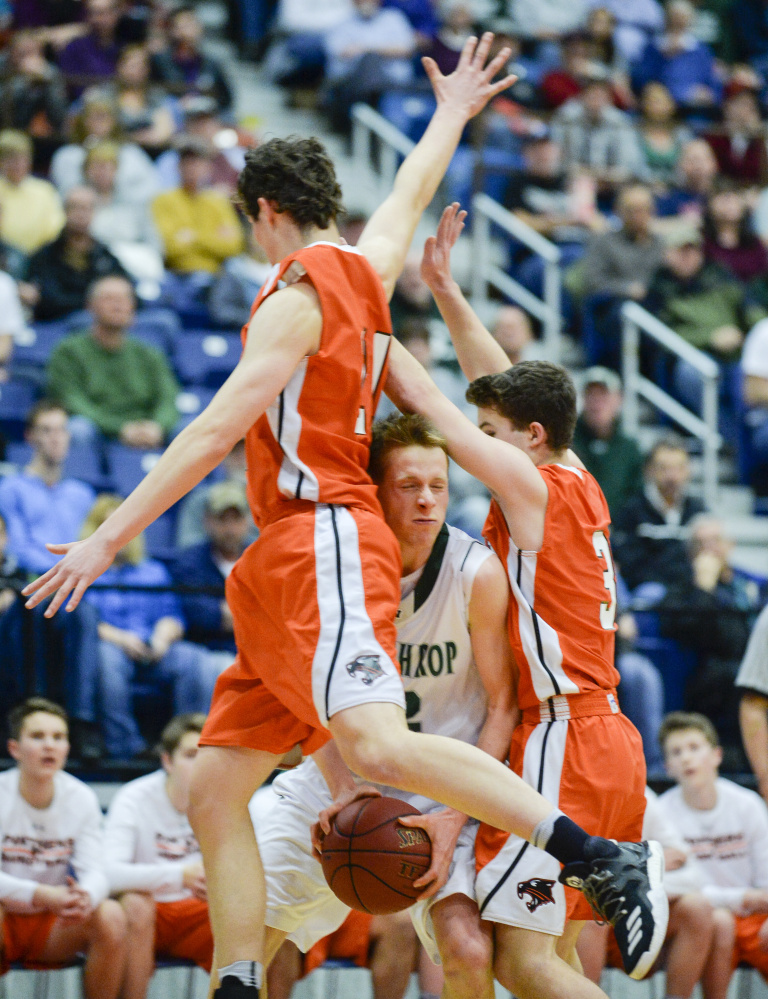 Winthrop's Jacob Hickey gets smashed between North Yarmouth Academy defenders Jake Malcom, left, and Davis Newell in the first quarter of the Class C South semifinal Thursday at the Augusta Civic Center.