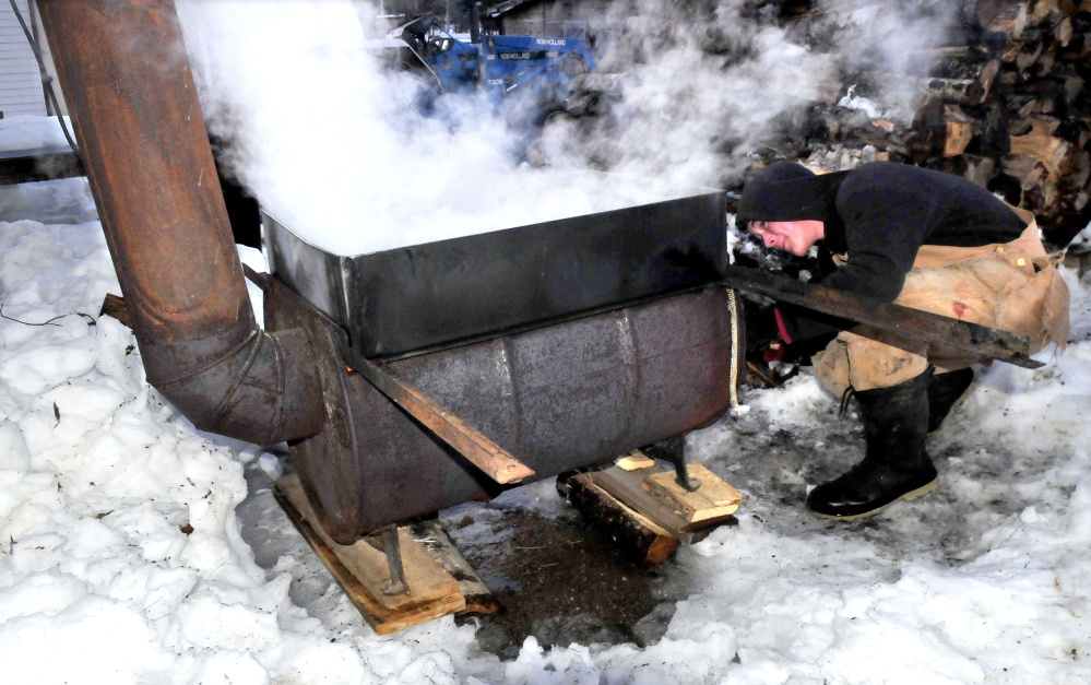 Steam rises as Addison Astbury stokes an evaporator with wood while boiling down maple sap into syrup at his home in Troy on Wednesday. Astbury said he has collected fast dripping sap for two warm days this week before beginning boiling.