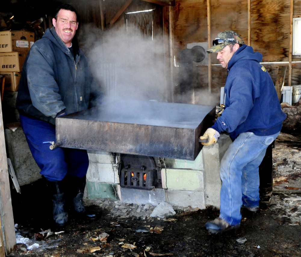 Paul Elkins, left, and Kurt Parker lift a tray of boiling maple syrup off a fire pit to pour into containers at their sap house in Thorndike on Thursday. Elkins said that, weather permitting, the pair and neighbor Ray Peabody will tap 60 trees and produce 25 gallons of syrup.