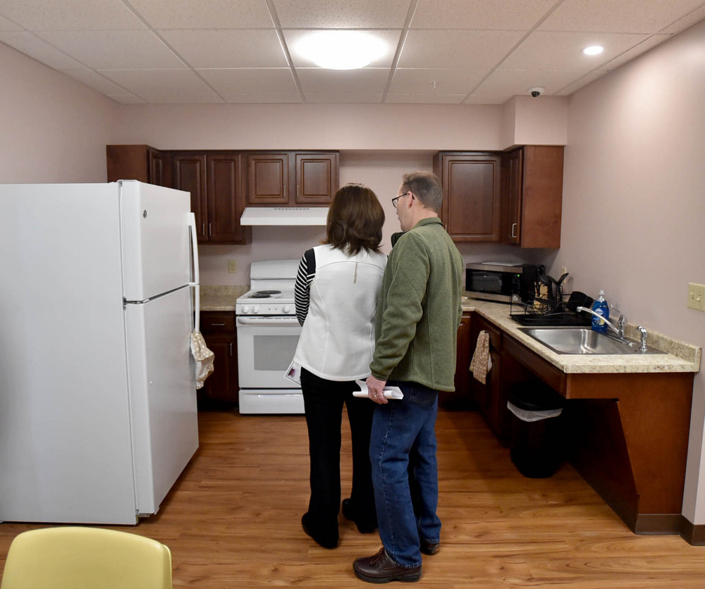 People tour the newly built apartments on the second floor of the Mid-Maine Homeless Shelter in Waterville on Friday.