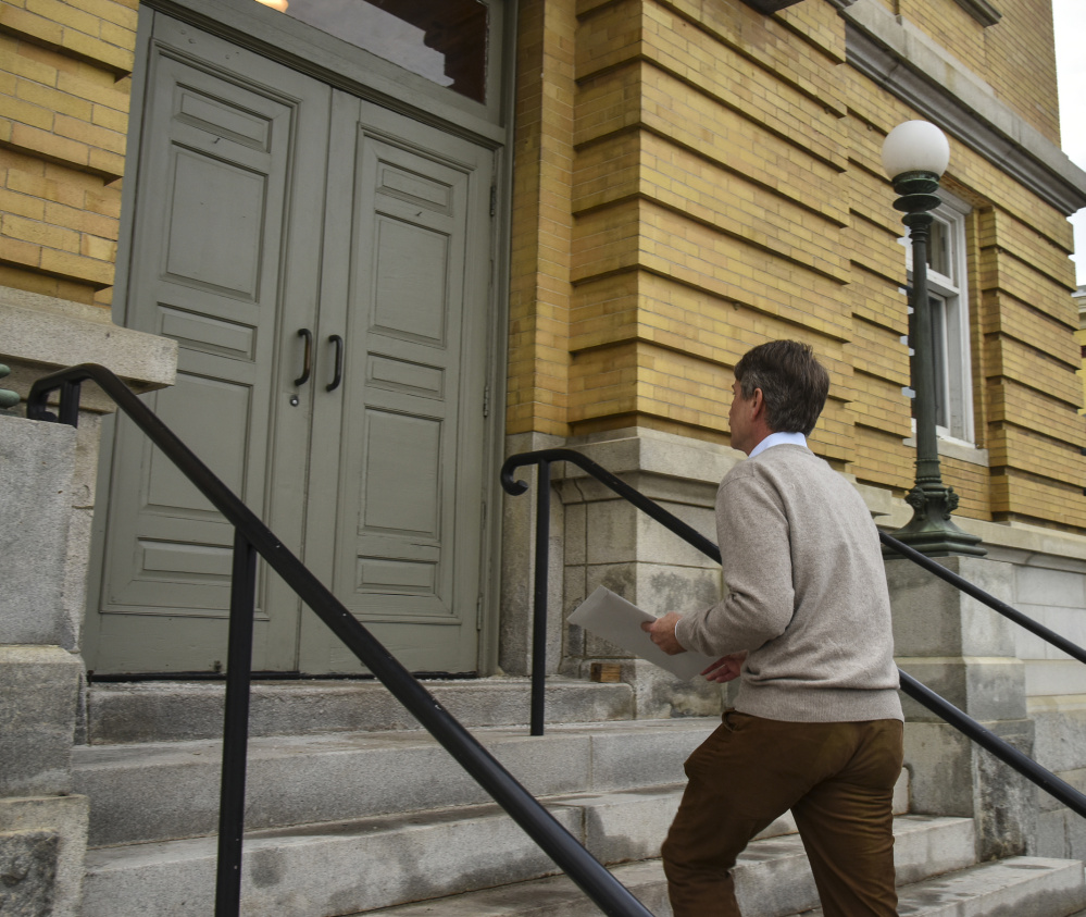 Stephen Langsdorf walks up the steps at Hallowell City Hall Friday to turn in a petition he's been circulating to require the City Council to reconsider its decision on fire services. He was required to get at least 216 signatures and turned in 288.