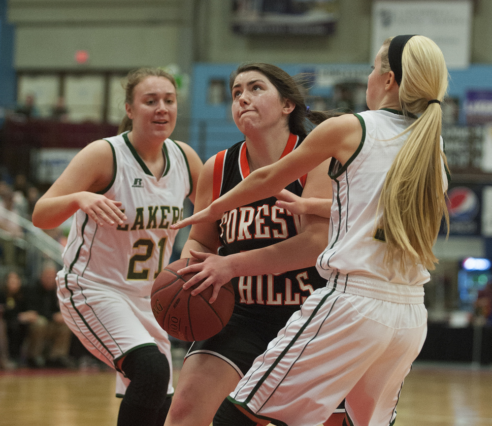 Kevin Bennett photo Forest Hills' Patricia Lessard splits Rangely's Celia Philbrick, left and Lauren Eastlack, right, during a Class D South semifinal at the Augusta Civic Center in Augusta on Thursday.