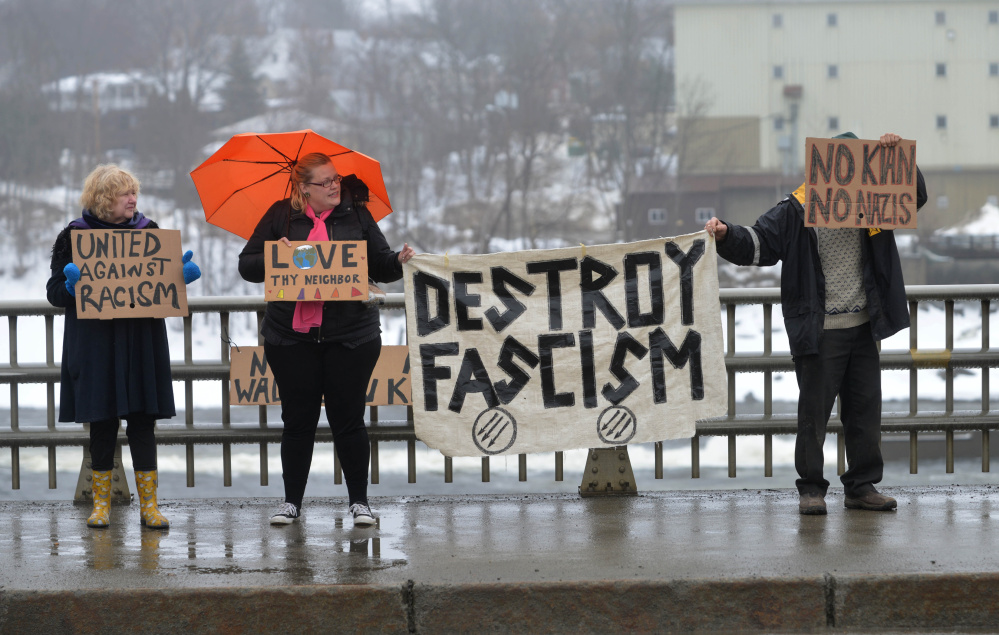 Protesters Beatrice Borden, far left, Serena Sanborn, left center and a man who would not identify himself stand on the Margaret Chase Smith Bridges in Skowhegan on Saturday to protest the Ku Klux Klan.