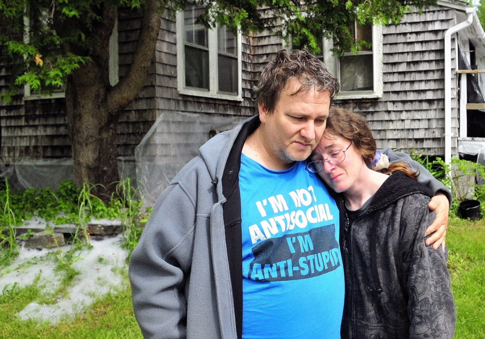 Patrick Lunt, left, hugs his wife, Beth Lunt, after an early morning fire on May 31, 2014, heavily damaged their home at 4 Pine Knoll Road in Winthrop. Patrick Lunt called her a hero for noticing the fire and getting him, their 19-year-old son Storme Lunt and another man up and out of the house.