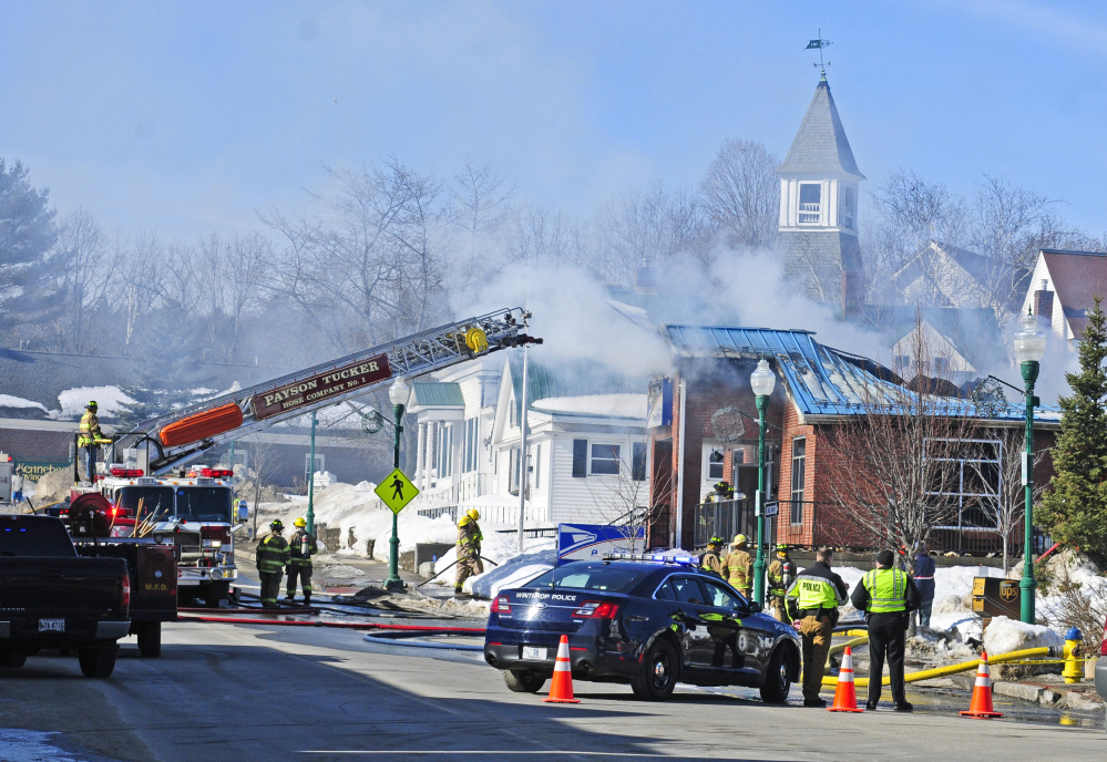 Firefighters work on Feb. 21 at the Winthrop post office, trying to quell the fire in the building that will now have to be demolished.