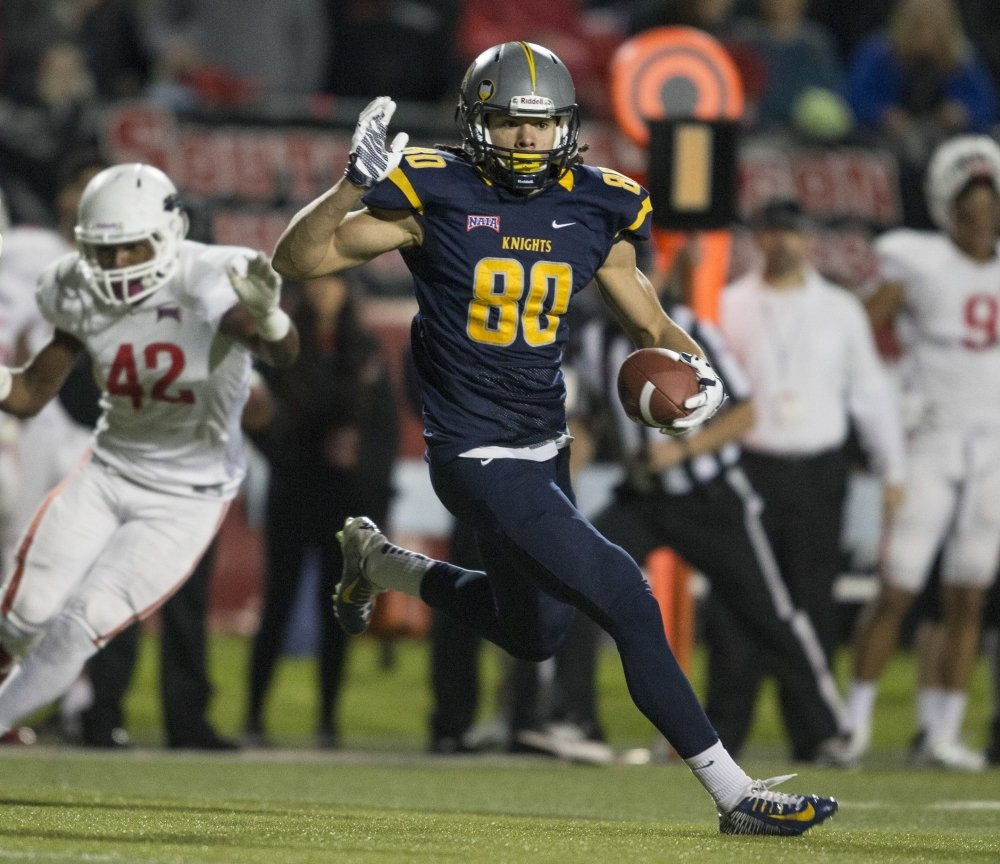 Marian wide receiver Krishawn Hogan (80) runs following a reception during the first half of the 2015 NAIA championship football game against Southern Oregon in Daytona Beach, Florida. Connor Harris and Krishawn Hogan started this year by explaining where they played college football. This week, they'll be on the same stage as the guys they watched on Saturday nights.