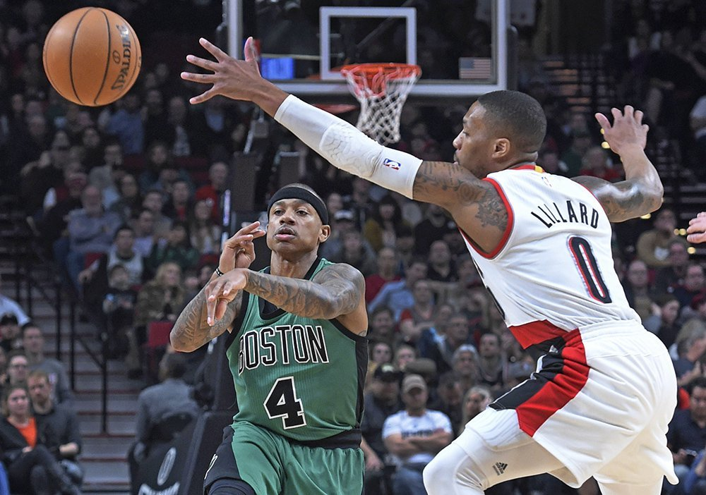 Boston Celtics guard Isaiah Thomas passes the ball past Trail Blazers guard Damian Lillard during the first half of Thursday night's game in Portland, Ore.