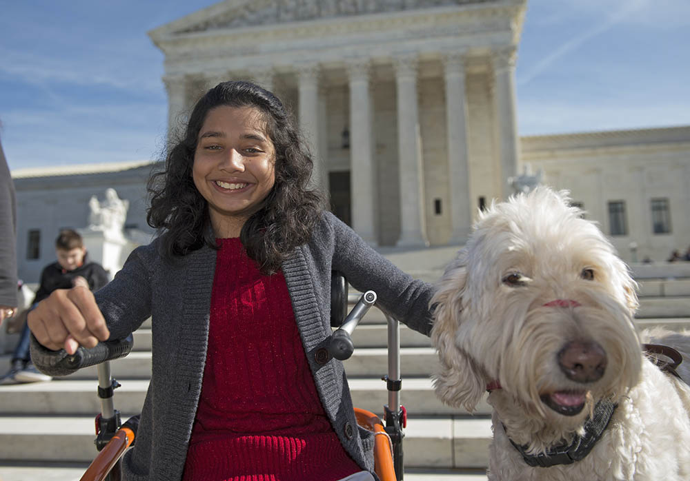 Ehlena Fry of Michigan and her service dog Wonder speaks to reporters outside the Supreme Court in Washington on Oct. 31, 2016.