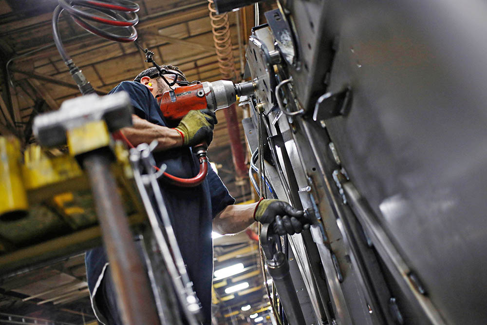 A worker installs components onto a New Holland Ltd. round baler at the company's Haytools factory in New Holland, Pennsylvania, on April 8, 2016. The low number of jobless claims suggests that employers feel they need to hang on to their workers in a tight labor market