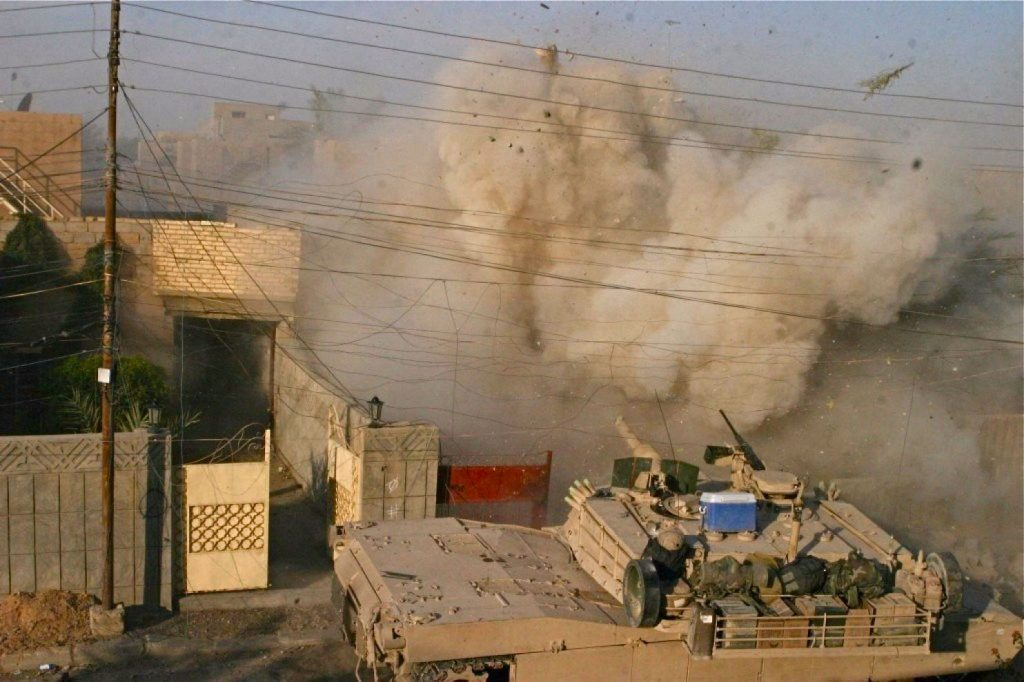 An M1A1 Abrams tank (in foreground with ice chest on top) with the 2nd Tank Battalion fires into a building that Marines received fire from during a battle in Fallujah in 2004.