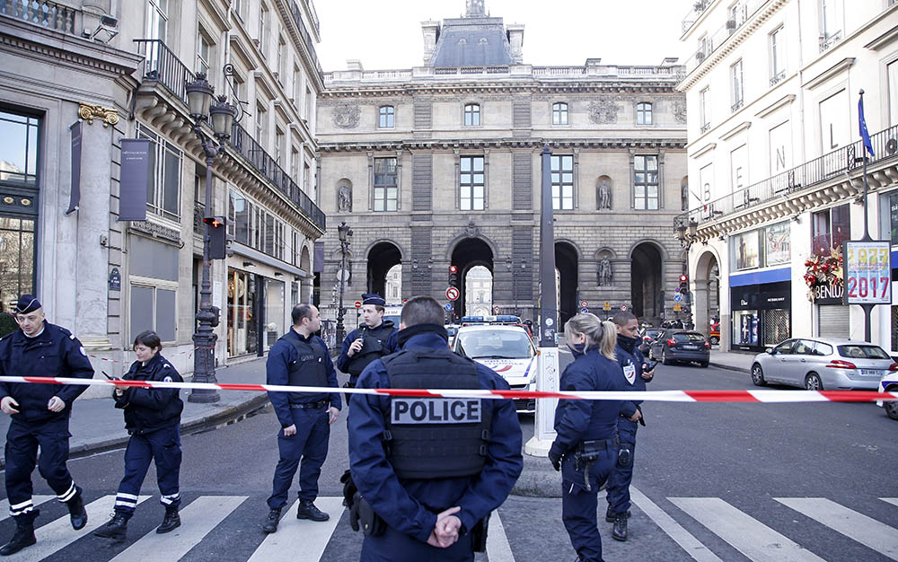 Police officers cordon off an area next to the Louvre in Paris Friday. Police say a soldier opened fire on an attacker  in an underground mall beneath the museum.