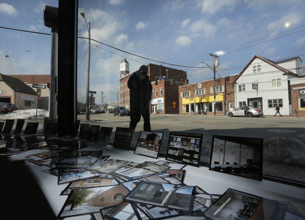 A man walks along a sidewalk on Forest Avenue outside the Speedwell Projects contemporary art gallery where small photographic prints fill a window display area. Artists are leading a Forest Avenue renaissance with the new contemporary art gallery, the return to Portland of a longstanding photography co-op and the emergence of a black box theater that is popular with theater groups and dancers.