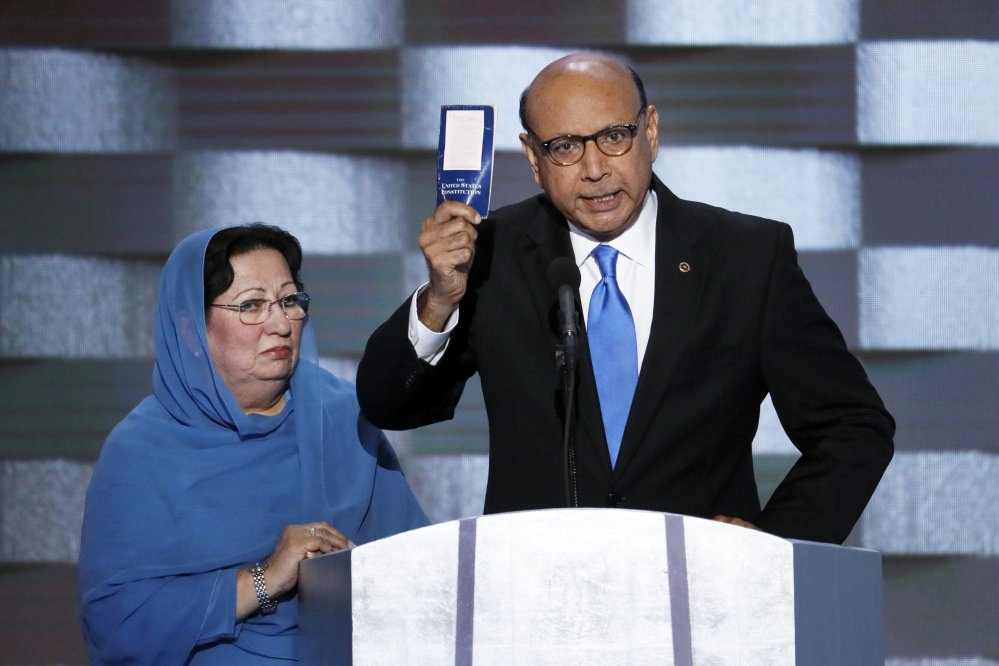 "Khizr Khan, father of fallen U.S. Army Capt. Humayun S. M. Khan, holds up a copy of the Constitution of the United States as his wife, Ghazala, listens during his speech to the Democratic National Convention in July. Khan, who is a longtime naturalized U.S. citizen, has been told his travel privileges are ""under review"" but has been given no reason."
