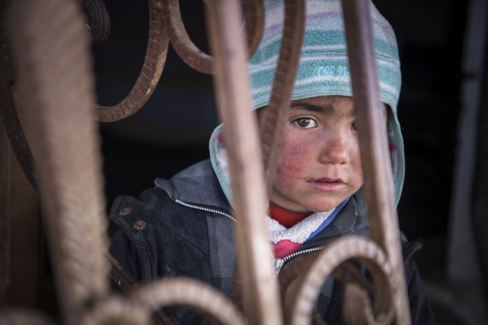 "A Syrian child looks out from an abandoned gas station where he and his family now live. A new report by Save the Children says Syrian children are showing symptoms of ""toxic stress"" from war exposure, and attempting self-harm and suicide."
