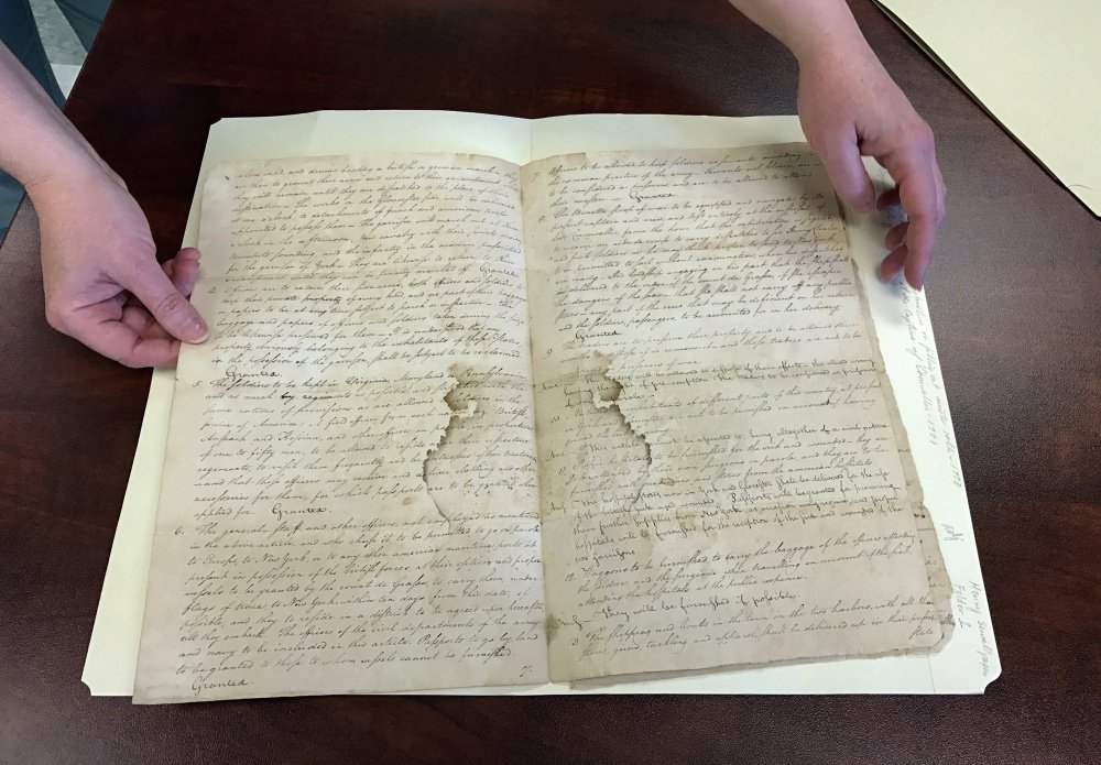 """Archivist Heather Moran displays a 1781 copy of the """"Articles of Capitulation,"""" which lays out the terms of British surrender after the Battle of Yorktown. The document is one of hundreds in the collection of the Maine State Archives that are awaiting transcription."""