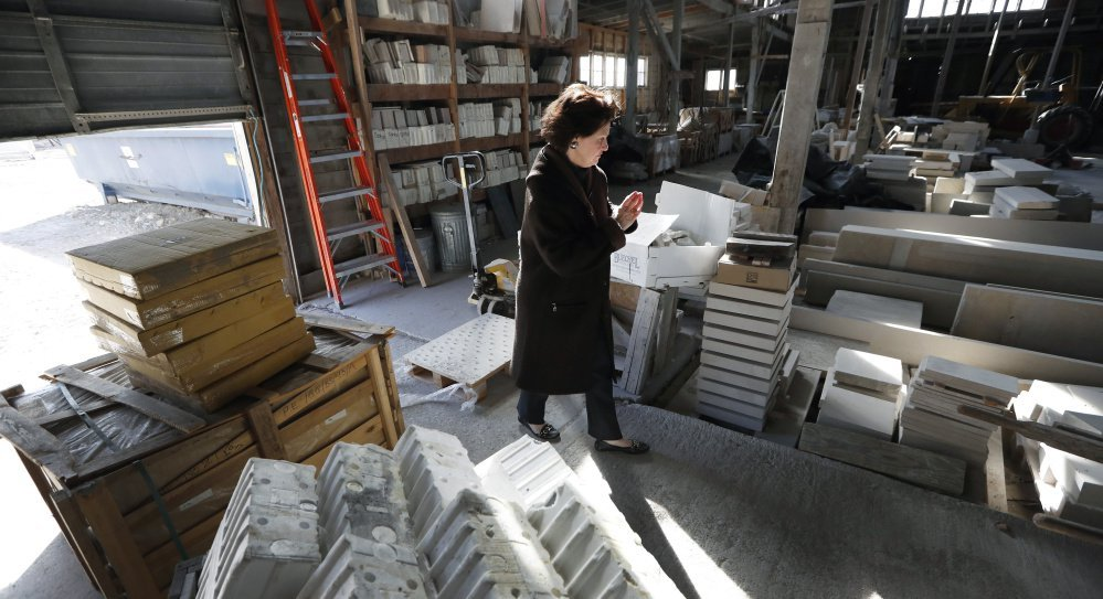 "Owner Teresa Van Vleet-Danos walks through the production area in the Rowat Cut Stone & Marble plant in Des Moines, Iowa. ""I love this old building,"" she said, but it will be torn down this summer and replaced with apartment towers."