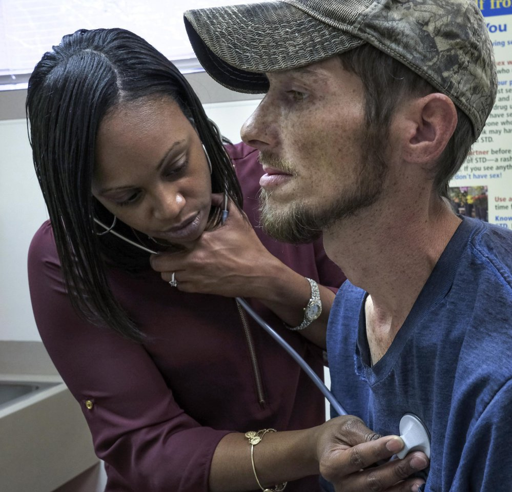 Nurse practitioner Keisha Saunders, who grew up in the community, examines Clarence Workman at the Tug River health clinic in Northfork, W.Va.
