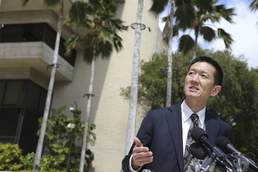 Hawaii Attorney General Douglas Chin speaks at a press conference Wednesday outside the federal courthouse in Honolulu, where a judge suspended President Trump's revised travel ban. The state filed a lawsuit claiming that the ban would harm Hawaii.