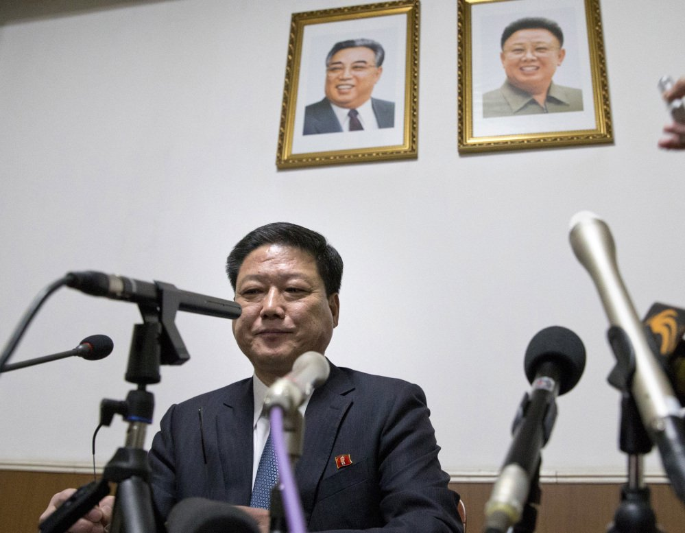Pak Myong Ho, minister of the North Korean Embassy in China, sits under portraits of the late North Korean leaders Kim Il Sung, left, and Kim Jong Il, on Thursday as he warns the West that North Korea is prepared to act in self-defense.