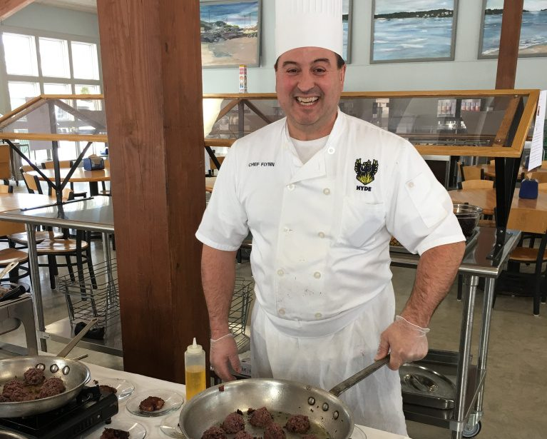 Hyde School chef Michael Flynn prepares samples of the vegan Crispy Blueberry Burger in the boarding school's dining hall.