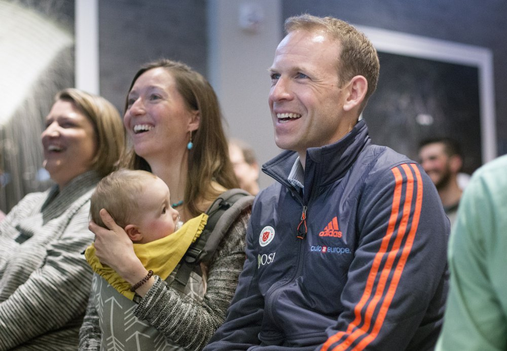 Lowell Bailey watches a recap of the biathlon world championships at Tuesday's press conference at the Press Hotel in Portland with his wife, Erika, and daughter, Ophelia.