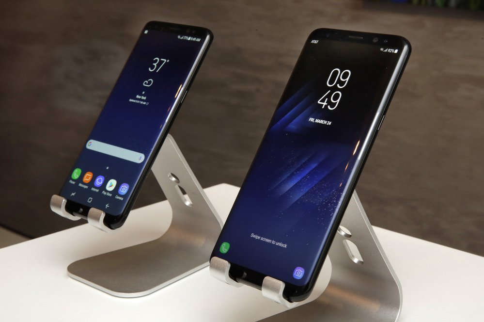 The new Samsung Galaxy S8, left, and S8 Plus are displayed in New York City. An optional docking station will turn an S8 into a desktop computer when connected to a regular TV.