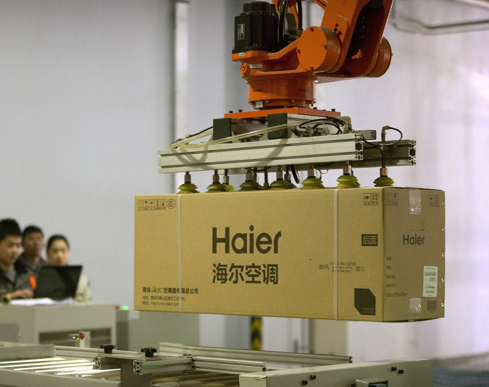 Factory workers watch a machine use suction to lift a box containing an air conditioner at a Haier factory in eastern China. Haier is now the biggest maker of major appliances.