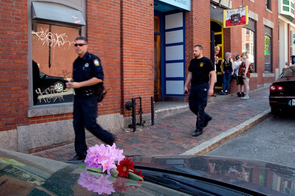 Portland police officers walk past flowers placed on the car that Treyjon Arsenault was driving on the night in 2015 when he was killed in a shooting at 26 Market St. in the Old Port.