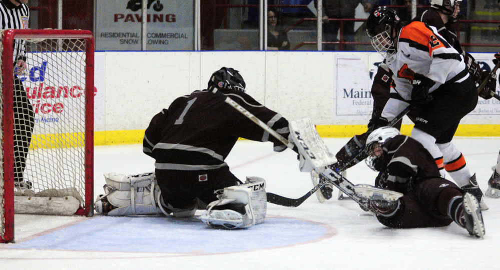 Greely goalie Josh Lawless, left, and defenseman Ben Kennedy block a shot by Gardiner forward Jacob Folsom in a Class B South semifinal game Friday night at the Androscoggin Bank Colisée in Lewiston.