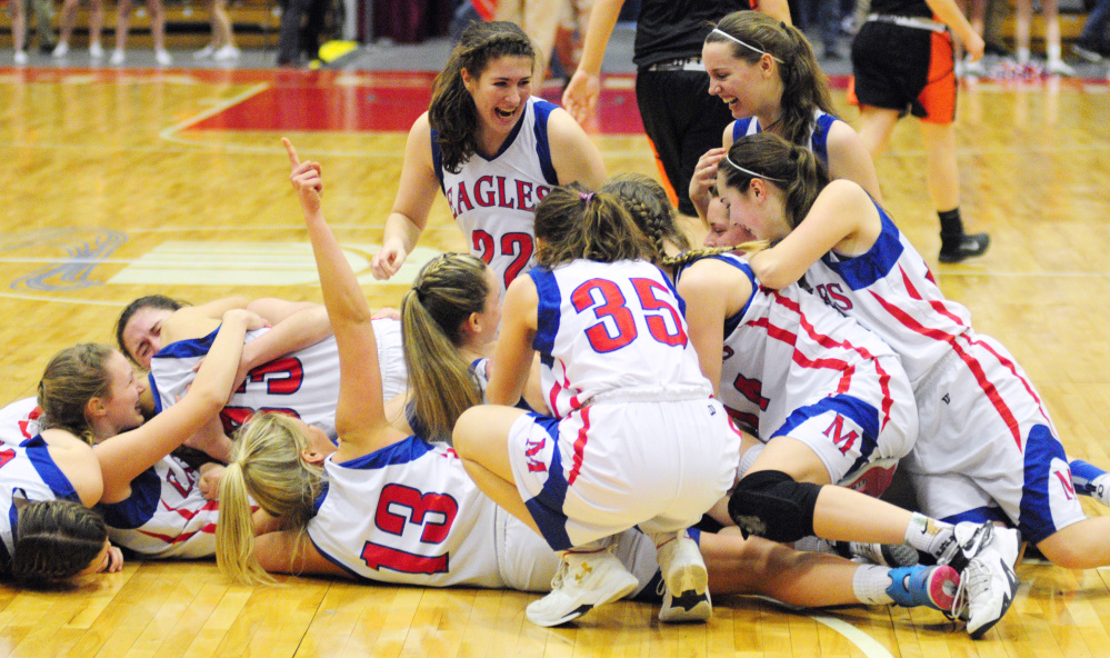 Messalonskee players celebrate at mid-court after beating Brunswick in the Class A state final Saturday at the Augusta Civic Center.