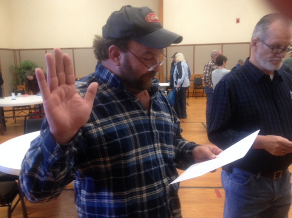 Embden Road Commissioner Michael Witham takes the oath of office Saturday following his re-election in Town Meeting voting. Newly elected Selectman Wayne McLaughlin, right, awaits his turn to take the oath.