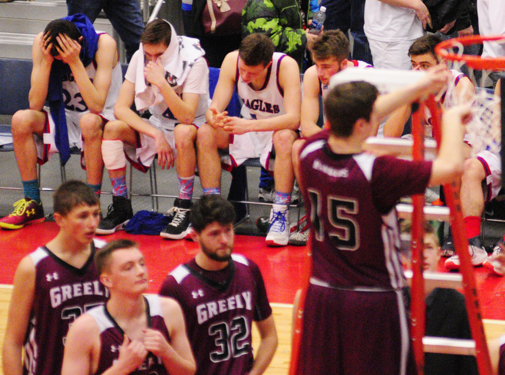 Messalonskee players look away as Greely's Andrew Miller cuts down the net after Rangers won the Class A state championship Saturday at the Augusta Civic Center.