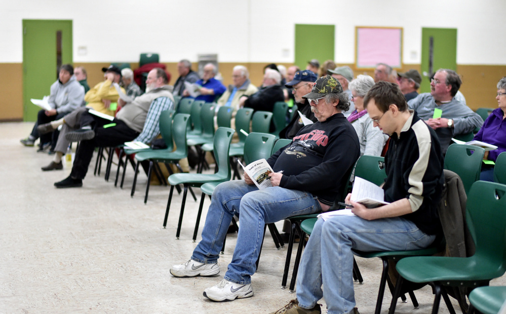Anson residents read through the many articles to be voted on Saturday during the annual town meeting at Carrabec High School in Anson.