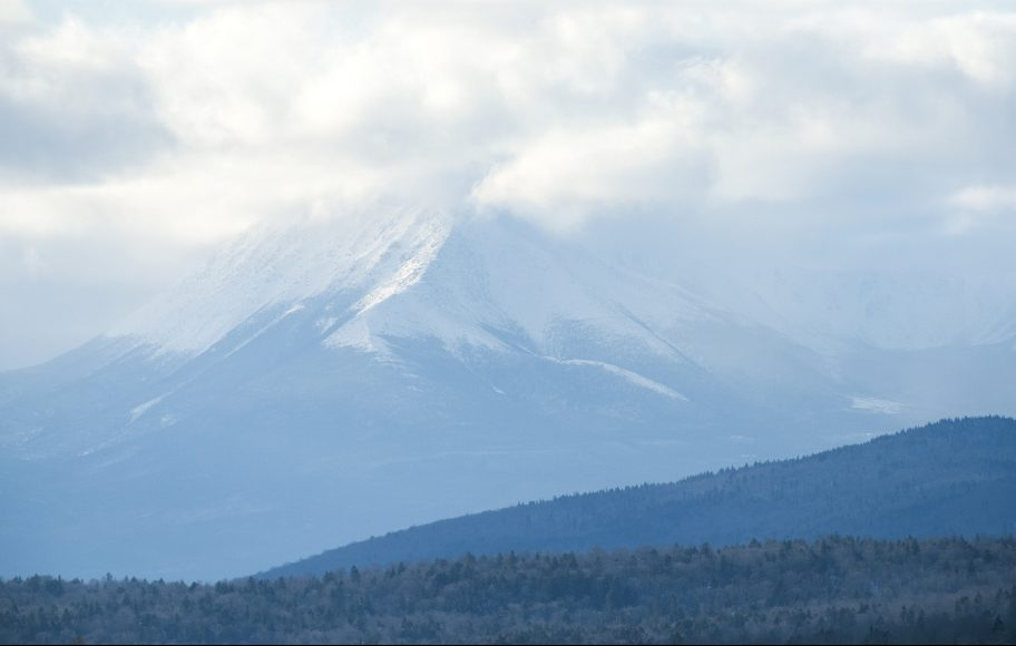 Snow and clouds obscure the peak of Mt. Katahdin, as seen from Patten. Mt Katahdin sits within Baxter State Park, which borders the Katahdin Woods and Waters National Monument.