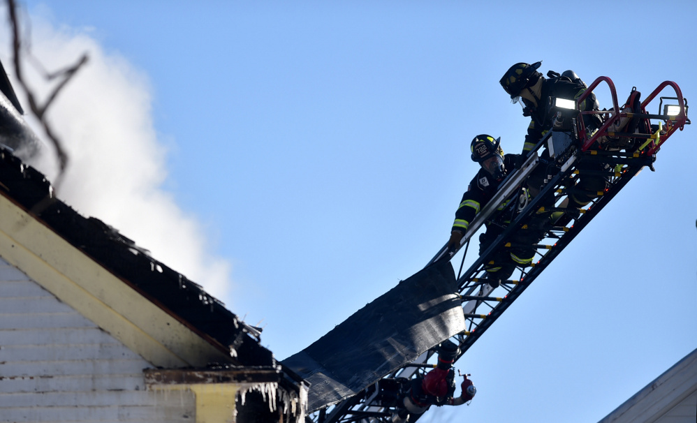 Firefighters from several towns battle a blaze Saturday afternoon on Main Street in Madison.