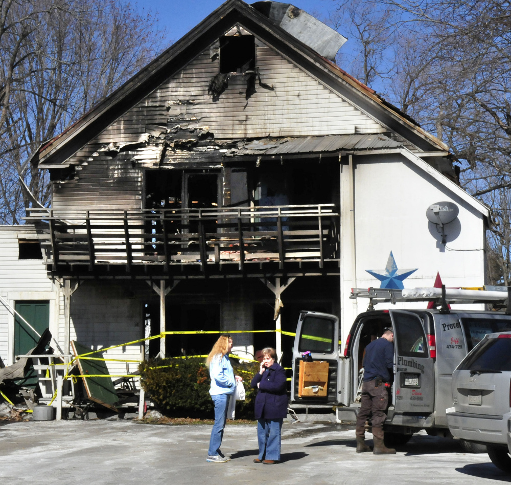 Madison apartment building owner Virginia Weems, right, speaks on a cellphone beside tenant Barbara Turner as a plumber makes repairs on Monday. Four of the building's seven apartments were destroyed by fire Saturday. The apartment Turner lives in with her husband did not burn but sustained smoke damage.
